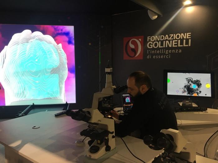 Sullo schermo più piccolo si possono osservare varie forme colorate che corrispondono ai movimenti dei microrganismi all'interno della goccia d'acqua. Contemporaneamente viene proiettato il tutto sul grande schermo che, grazie alla tecnica del 3D mapping, crea un'opera d'arte.